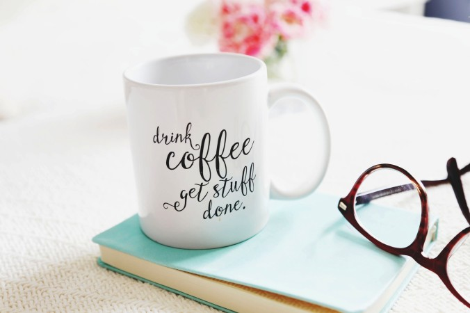 drink-coffee-from-white-mug-with-glasses-and-book-on-wooden-table